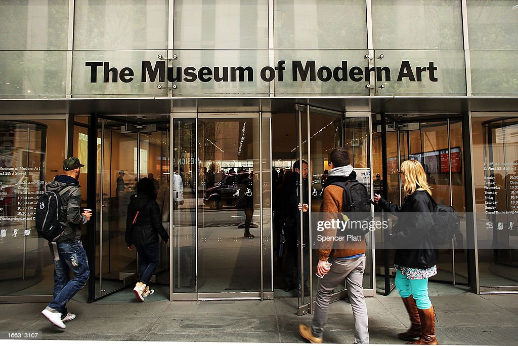 People walk into the Museum of Modern Art on April 11 2013 in New York City MoMA announced yesterday that it will demolish the former Museum of...