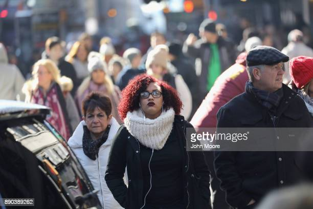 People walk into Times Square in Midtown Manhattan near the site of a pipe bomb explosion on December 11 2017 in New York City Police said that...