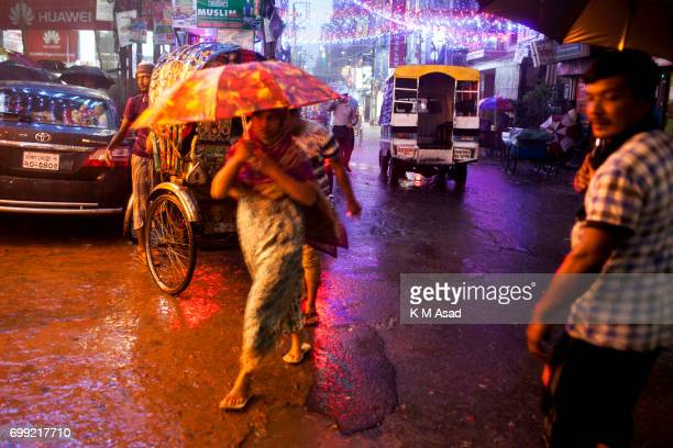 OLD DHAKA DHAKA BANGLADESH People walk middle in the rain when heavy rainfall made in Dhaka city The death toll rises to 150 in several hill...