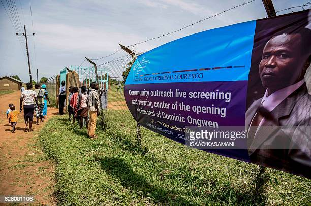 People walk near a banner of former child soldierturnedwarlord Dominic Ongwen before the screening of the start of his ICC trial in Lukodi Uganda on...