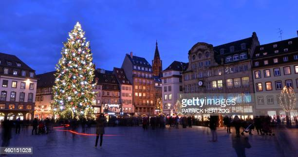 People walk near a giant Christmas tree in Strasbourg eastern France on December 8 during the city's Christmas market the largest and one of the...