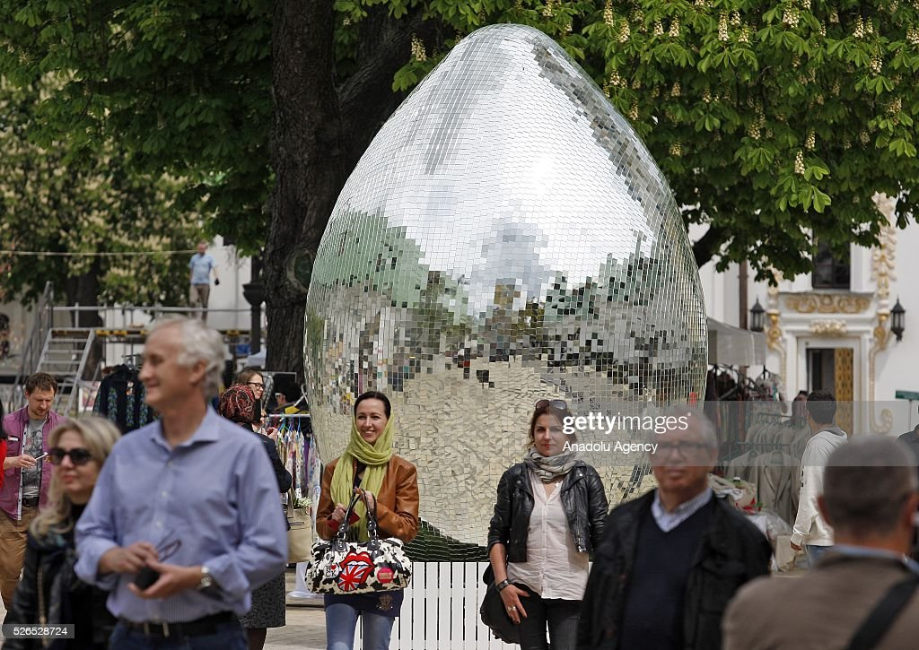 People walk near a giant egg, named 'Diamond Easter Egg',3.5 m high, which is decorated with more than 15,000 mirror particles during the Ukrainian Easter hand made fair 'Easter country' at the Kiev-Pechersk Lavra in Kiev, Ukraine on April 30, 2016.
