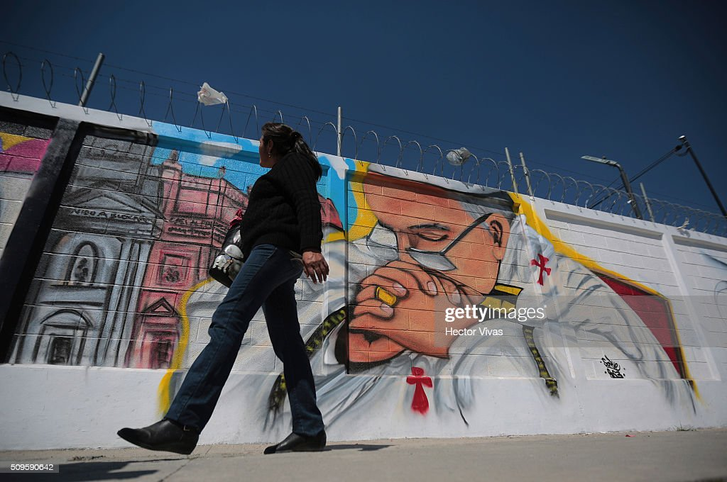 People walk near a graffiti painted to welcome Pope Francis near the esplanade where Pope Francis will give a mass for 300 thousand people during the preparations ahead the visit of Pope Francis to Mexico at Las Americas on February 11, 2016 in Ecatepec, Mexico.