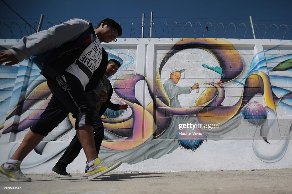 People walk near a graffiti walls painted to welcome Pope Francis near the esplanade where Pope Francis will give a mass for 300 thousand people during the preparations ahead the visit of Pope Francis to Mexico at Las Americas on February 11, 2016 in Ecatepec, Mexico.