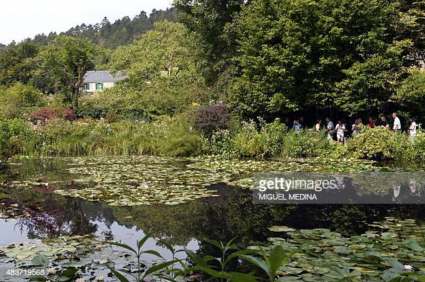 People walk near a pond with lilypads as they visit the gardens of the home of French Impressionist painter Claude Monet in Giverny northwestern...