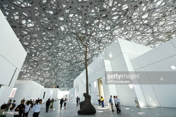 People walk near a sculpture by Italian artist Giuseppe Penone at the Louvre Abu Dhabi Museum on November 7 on the eve of the official opening of the...