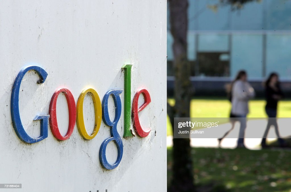 People walk near a sign outside of Google headquarters January 31 2007 in Mountain View California Google Inc reported its fourth quarter earnings...