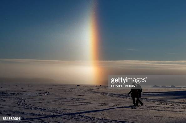 TOPSHOT People walk near a solar halo on the frozen sea in Vaasa by 15°C on January 15 2017 The Halo is an optical phenomena produced by light...