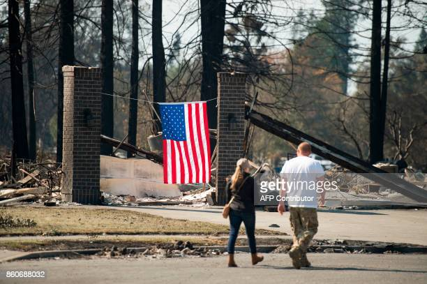 People walk near an US flag hung on a burned property in Santa Rosa California on October 12 2017 Hundreds of people are still missing in massive...