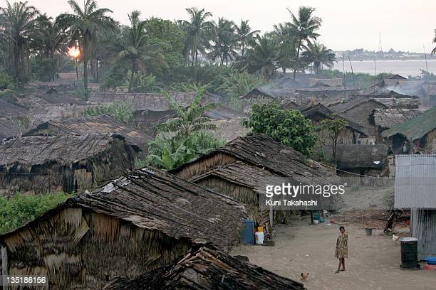 People walk near buildings on November 4 2005 in the fishing village of Itak Abasi in the Niger Delta Nigeria The delta is an oilrich region and has...