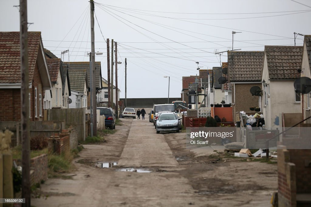 People walk near dilapidated properties stand in the seaside town of East Jaywick, the most deprived place in England, on April 3, 2013 in Jaywick, England. The Government's 2011 Indices of Multiple Deprivation' measure ranks Jaywick as the most deprived of all 32,482 small wards in England and Wales. The area also has the greatest number of young people not in employment, education or training; one third of 16 to 24 year-olds claim Jobseeker's Allowance, compared to the national average of 6 per cent. Changes to the benefits and tax system which came into force on April 1, 2013 have included a cut in housing benefit payments for working-age social housing tenants whose property is deemed larger than they need and council tax support payments now being administered locally.
