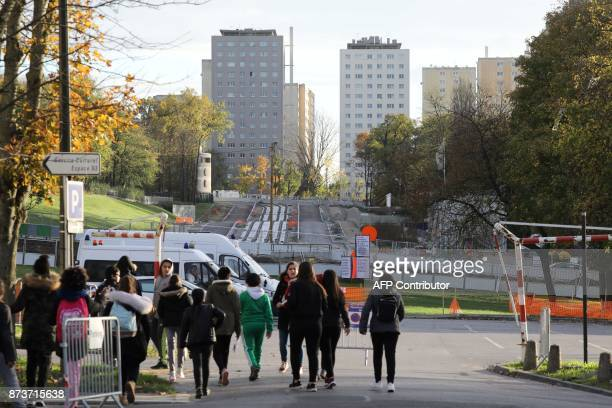 People walk near the construction site of public transportation on November 13 in ClichysousBois northern Paris / AFP PHOTO / LUDOVIC MARIN