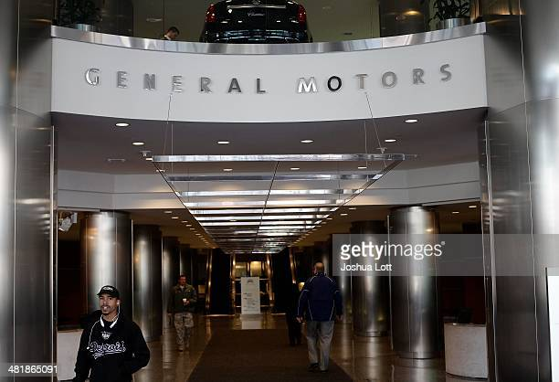 People walk near the front entrance of the General Motors headquarters April 1 2014 in Detroit Michigan General Motors has recalled millions of...