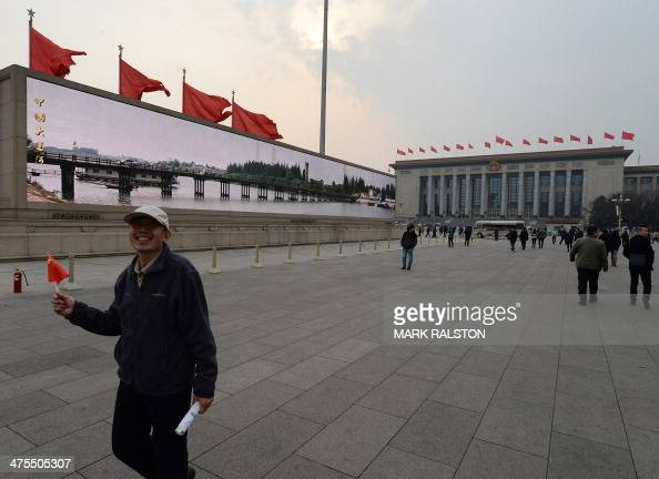 People walk near the Great Hall of the People where the upcoming opening sessions of the Chinese People's Political Consultative Conference and the...
