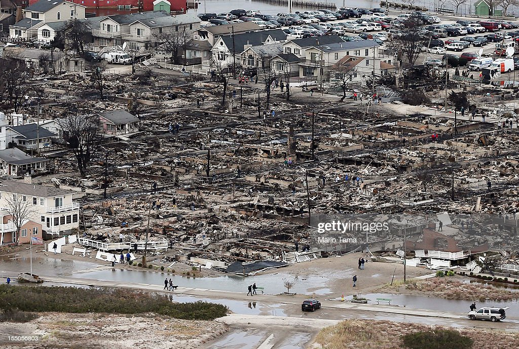 People walk near the remains of burned homes after Hurricane Sandy on October 31, 2012 in the Breezy Point neighborhood of the Queens borough of New York City. Over 50 homes were reportedly destroyed in a fire during the storm. At least 50 people were reportedly killed in the U.S. by Sandy. New York City was hit especially hard with wide spread power outages and significant flooding in parts of the city.