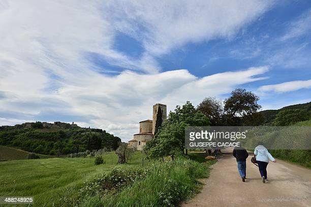 People walk near the Sant'Antimo Abbey in Montalcino near Siena on May 4 2014 AFP PHOTO / GIUSEPPE CACACE