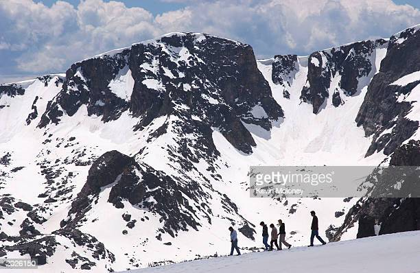 People walk near the Trail Ridge Road May 23 2003 in Rocky Mountain National Park Colorado The road was opened for the season May 23 after crews...