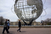 People walk near the Unisphere near the New York State Pavilion as part on a tour during festivities marking the 50th anniversary of the 1964 World's...