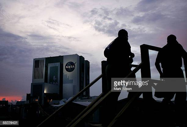 People walk near the Vehicle Assembly Building as the sun sets at the Kennedy Space Center July 12 2005 in Cape Canaveral Florida Earlier in the day...