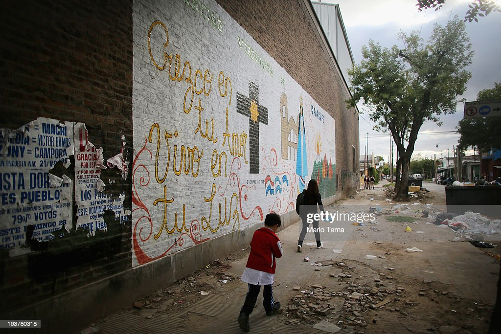 People walk near the Virgin of the Miracles of Caacupe church in the Villa 21-24 slum, where archbishop Jorge Mario Bergoglio, now Pope Francis, used to perform charity work, on March 15, 2013 in Buenos Aires, Argentina. Francis was the archbishop of Buenos Aires and is the first pope to hail from South America. Some locals are now affectionately calling Francis, known for his charity work in the slums, the 'slum pope.'