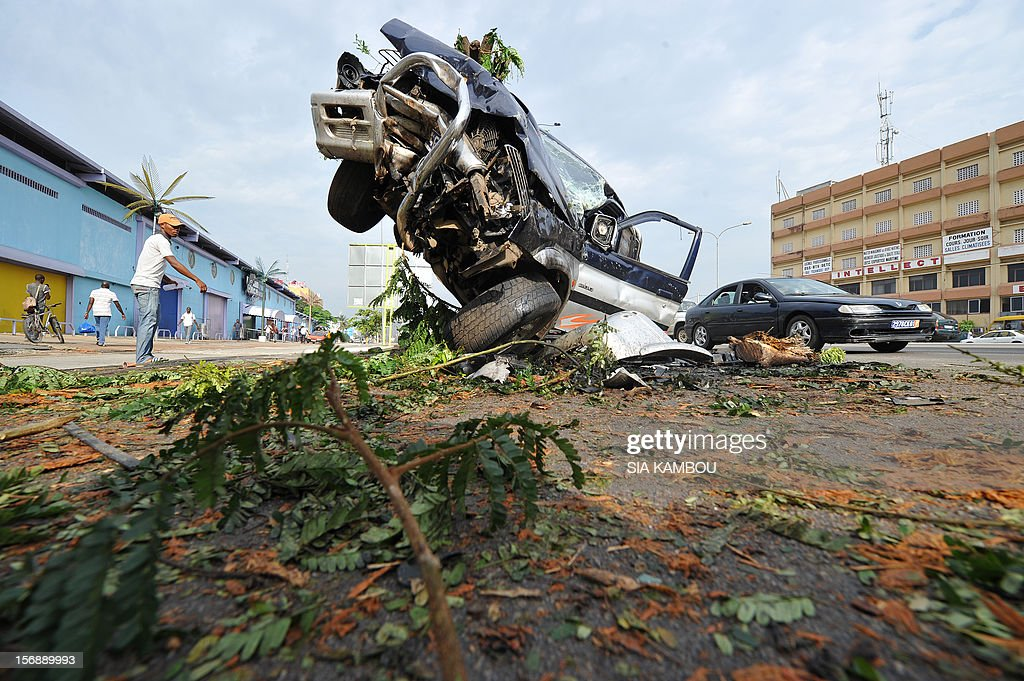 People walk near the wreck of a car after a road accident on November 24, 2012 in Abidjan. AFP PHOTO/ SIA KAMBOU