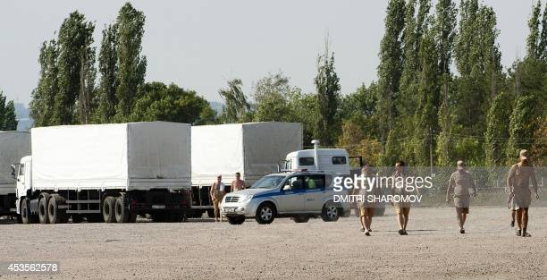 People walk near trucks of Russian humanitarian convoy waiting at the location outside Voronezh some 400 km outside Moscow on August 13 2014 A...