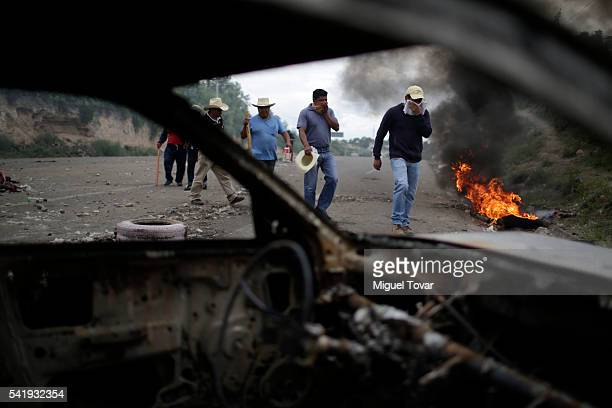 People walk next to a burned barricade a day after the clashes between striking teachers and police at the outskirt of Nochixtlan Mexico on June 20...