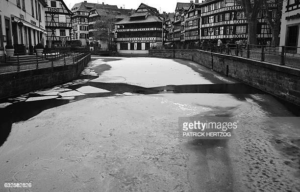 People walk next to a frozen river the Ill on January 24 2017 in the 'Petite France' district in central Strasbourg eastern France A toxic cocktail...
