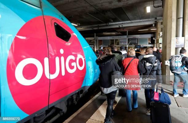 People walk next to a lowcost TGV highspeed train 'Ouigo' at Paris MontparnasseVaugirard railway station in Paris on December 10 2017 Trains of...