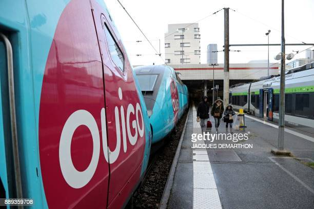 People walk next to a lowcost TGV highspeed train 'Ouigo' at Paris MontparnasseVaugirard railway station in Paris on December 10 2017 Trains of...