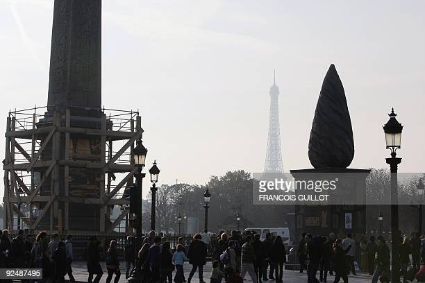 People walk next to a menhir and a base with Asterix and Cleopatra cartoon characters on it displayed Place de la Concorde in Paris as part of the...
