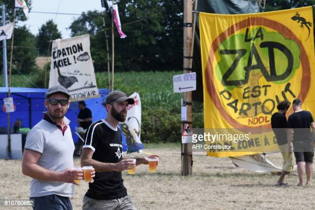 People walk next to a sign reading 'The ZAD is everywhere NDLL Zone to defend' during a twoday meeting organised by opponents to a controversial...