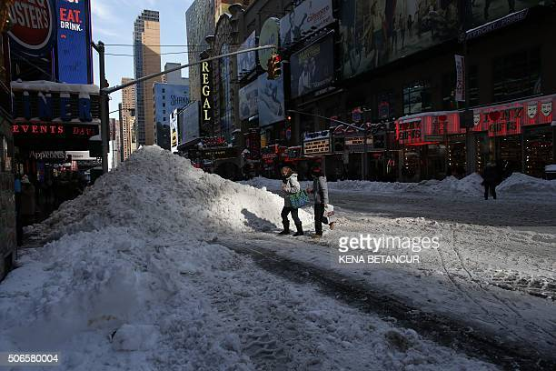 TOPSHOT People Walk next to a snow pile near Times Square on January 24 2016 in New York City A massive blizzard that claimed at least 16 lives in...