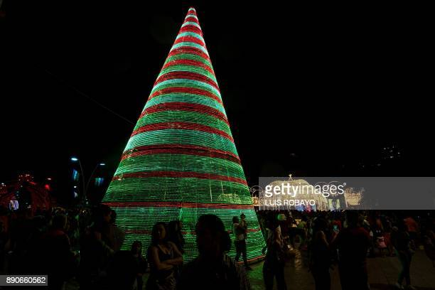 People walk next to Christmas decorations in Cali Colombia on December 11 2017 / AFP PHOTO / LUIS ROBAYO
