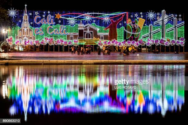 TOPSHOT People walk next to Christmas decorations in Cali Colombia on December 11 2017 / AFP PHOTO / LUIS ROBAYO