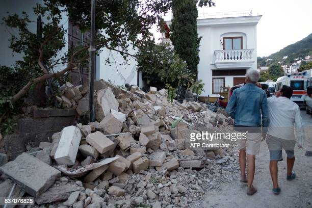 People walk next to collapsed houses in Casamicciola Terme on the Italian island of Ischia on August 22 after an earthquake hit the popular Italian...