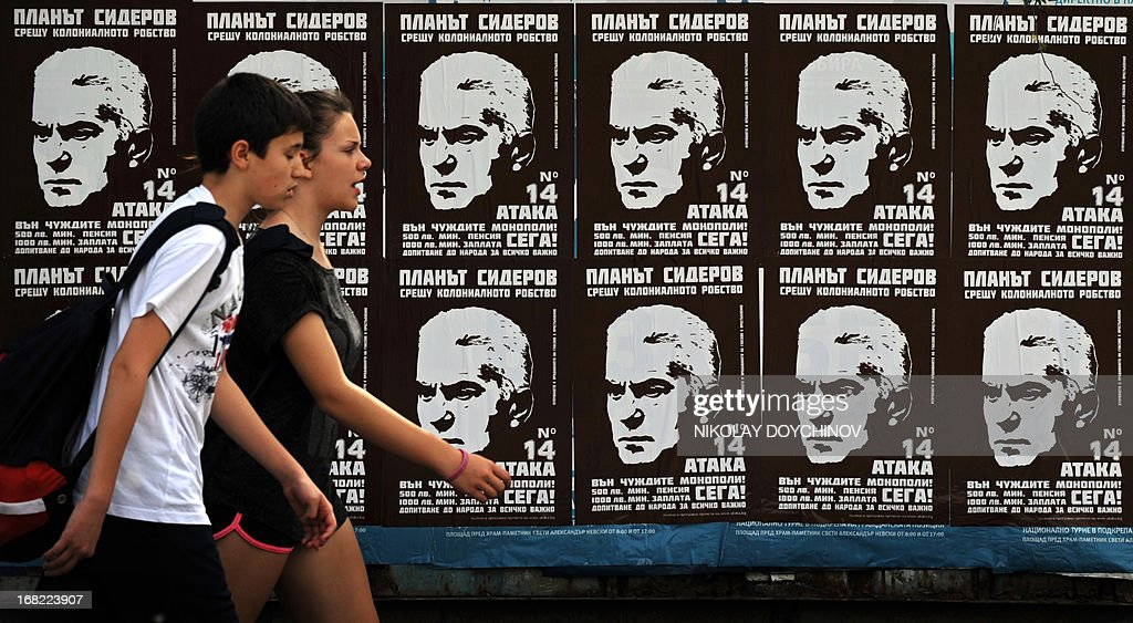 People walk next to election campaign posters supporting Volen Siderov, leader of the ultra-nationalist Ataka party, in Sofia on May 07, 2013. A winter of discontent in Bulgaria, when mass protests forced out the government, could give way to a spring of political deadlock and instability after elections Sunday in the EU's poorest country. AFP PHOTO / NIKOLAY DOYCHINOV