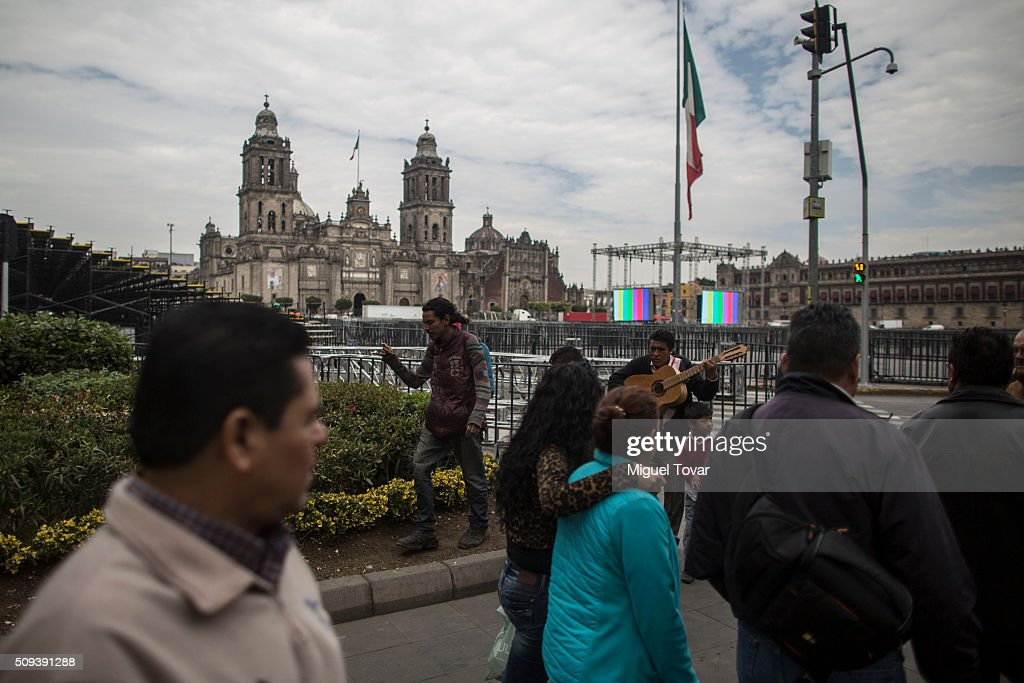 People walk next to fences installed at Zocalo Main Square on February 10, 2016 in Mexico City, Mexico. The Zocalo main square is closed to public, as the perimeter is prepared for the upcoming visit of Pope Francis on February 12-17.