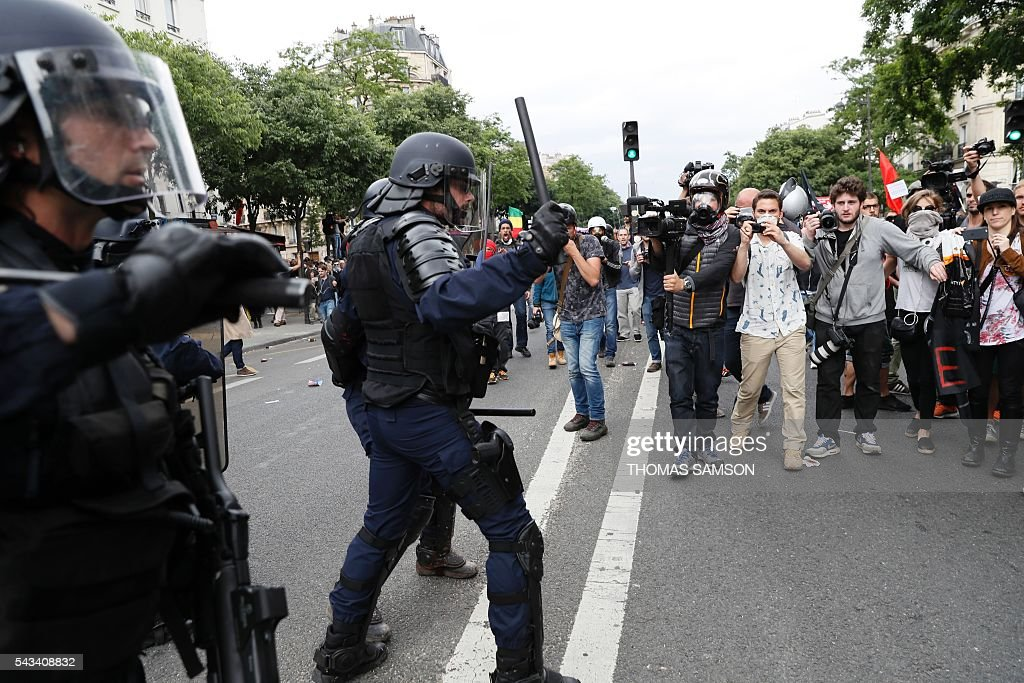 People walk next to French anti-riot police officers during a demonstration against controversial labour reforms, on June 28, 2016 in Paris. Unions have called repeated strikes and marches in opposition to the law, which seeks to bring down France's intractable 10-percent unemployment rate by making it easier to hire and fire workers. / AFP / Thomas SAMSON