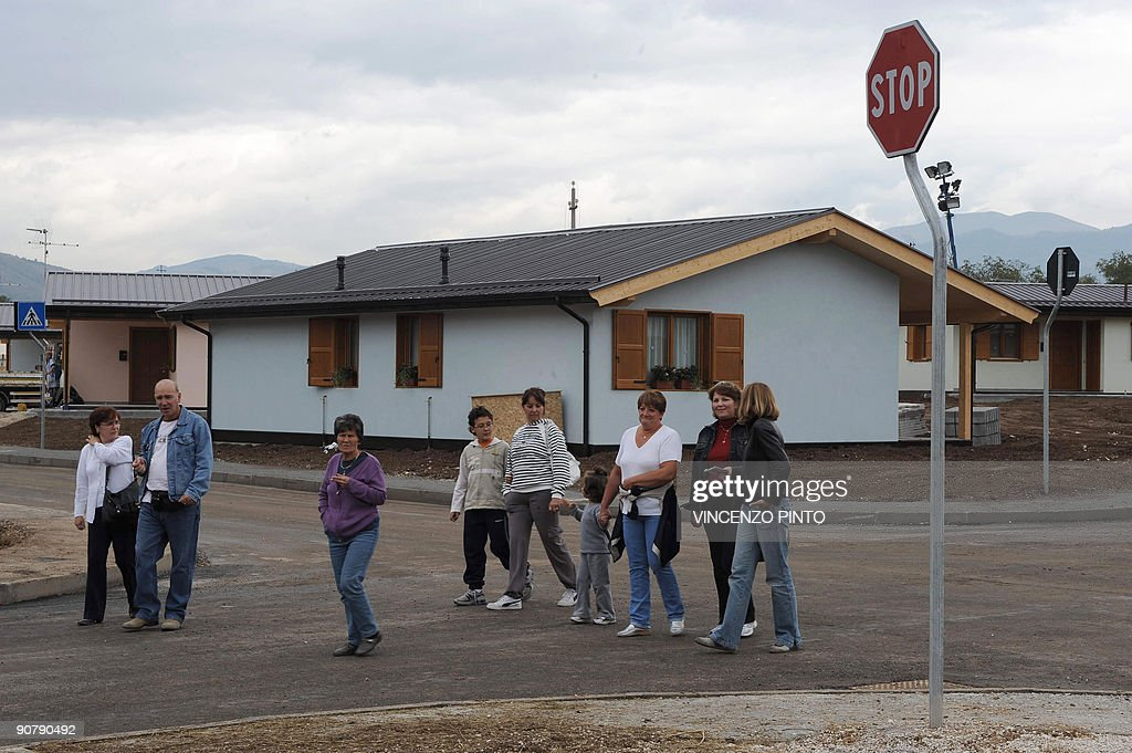 People walk next to some of the 94 houses built for the victims of the April 6 earthquake and inaugurated by Italian Prime Minister Silvio Berlusconi...