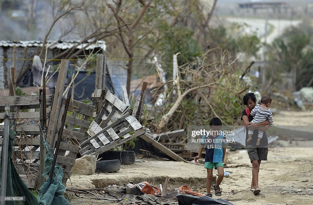 People walk next to the remains of a house at the El Vado Santa Rosa neighborhood after hurricane Odile in San Jose Los Cabos Baja California State...
