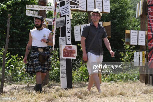 People walk next to totems with various slogans during a twoday meeting organised by opponents to a controversial international airport project in...