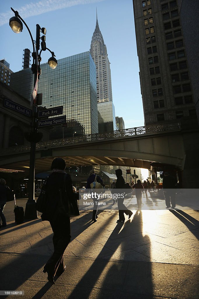 People walk on 42nd Street outside Grand Central Terminal as the sun rises during the morning rush near the Chrysler Building in Manhattan on November 1, 2012 in New York City. Some trains are back up and running into Grand Central following shutdowns in the aftermath of Superstorm Sandy. Subway train service in the city is back in a limited capacity, but with much of lower Manhattan still with out power, trains are not running there and busses are replacing them.