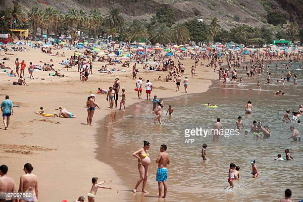 People walk on a beach on April 20 2013 on the Spanish Canary island of Tenerife where temperatures are soaring due to the Sirocco a Mediterranean...