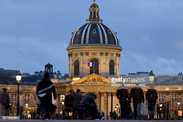 People walk on a bridge in front of the Institut de France building which houses the Academie Francaise in Paris on February 1 2016 / AFP / KENZO...