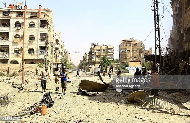 People walk on a damaged road after the war crafts belonging to the Syrian army bombed residential areas in the Douma district of the eastern Ghouta...