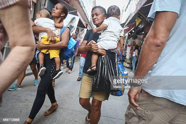 People walk on a downtown street on September 23 2015 in Rio de Janeiro Brazil The US dollar climbed to record highs against the Brazilian real...
