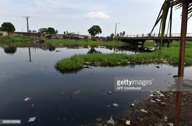 People walk on a footbridge overlooking a gutter filled up with wastewater and used oil in the Ebrie Lagoon which is suffering from pollution on June...