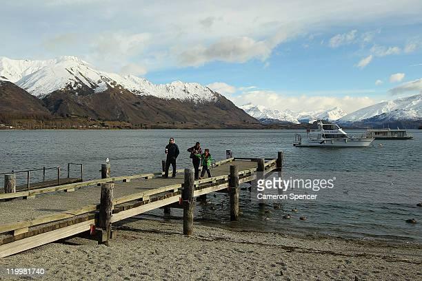 People walk on a jetty at Lake Wanaka on July 28 2011 in Wanaka New Zealand