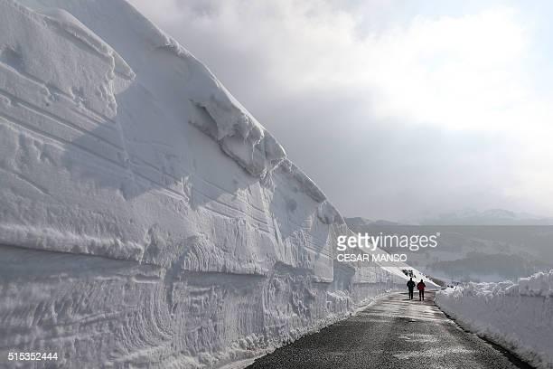 People walk on a road after heavy snowfall between Las Machorras and the ski resort of Lunada near Espinosa de los Monteros in the northern province...